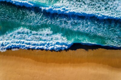 Aerial view of a wave breaking at the shore of the Comporta Beach in Portugal; Concept for travel in Portugal and summer vacations