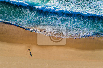Aerial view of a wave breaking at the shore of the Comporta Beach in Portugal, with a fisherman on the beach.
