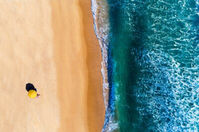 Aerial view of beach umbrella with a person sunbathing, at the Comporta Beach in Portugal. Concept for social distancing on the beach.