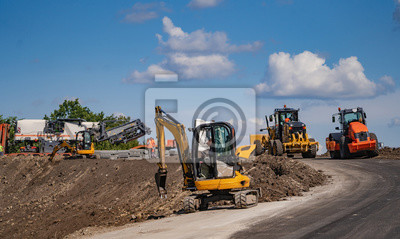 Obraz An excavator in a road construction site. Yellow special technic, machinery. Road repair concept.