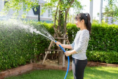 Asian woman having happy in home backyard summer garden, with garden hose splashing water on the lawn and tree leafs during Staying at home using free time about their daily housekeeping routine.