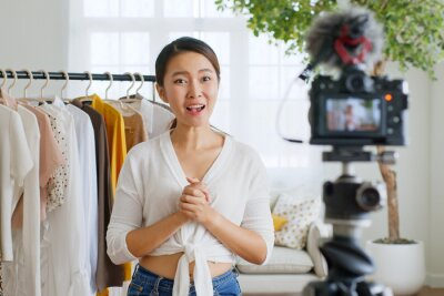 Obraz Asian woman influencer seller broadcast live streaming to sell clothes for online social marketing