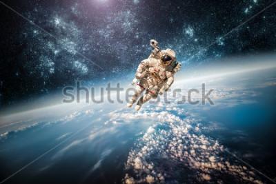 Obraz Astronauta kosmosie na tle planety Ziemia. Elementy tego obrazu dostarczone przez NASA.