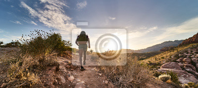 Obraz athletic african american woman hiking through red rock canyon in nevada at sunset