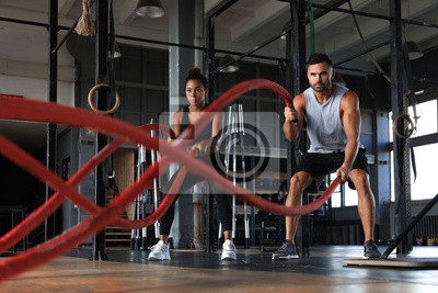 Obraz Athletic young couple with battle rope doing exercise in functional training fitness gym.