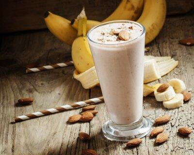 Obraz Banana smoothie z mlekiem, mielone migdały w dużym kubku w sprawie