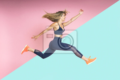 Obraz beautiful blond-haired woman with fitness lifestyle wearing sportswear is running and jumping with her hair in motion on an isolated background of various colors