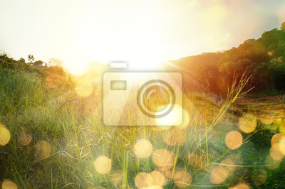 Obraz Beautiful sunrise in the mountain..Meadow landscape refreshment with sunray and golden bokeh.