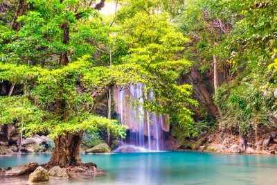 Beautiful waterfall in tropical jungle forest with big green tree and emerald lake on foreground. Nature landscape of Erawan National park, Kanchanaburi, Thailand