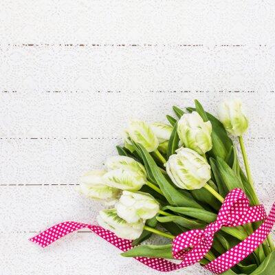 Obraz Białe tulipany ozdobione czerwoną wstążką na białym obrusem. Kopia przestrzeń, widok z góry