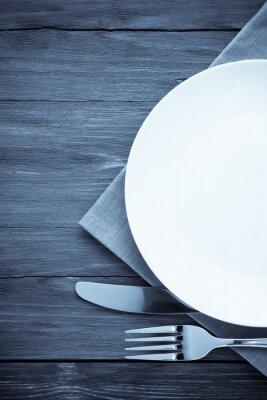Obraz biały talerz, nóż i widelec na drewnie