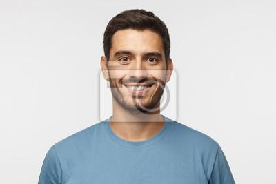Obraz Bliska portret młody uśmiechnięty przystojny facet w niebieską koszulkę na białym tle na szarym tle