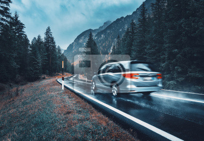 Obraz Blurred car in motion on the road in autumn forest in rain. Perfect asphalt mountain road in overcast rainy day. Roadway, pine trees in italian alps. Transportation. Highway in foggy woodland. Travel