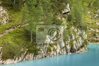 brzegiem jeziora z sosnami i niesamowitym kolorem jeziora we Włoszech