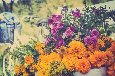 Obraz Bukiet kwiatów na białym krześle. Niewyraźne retro rower w bac