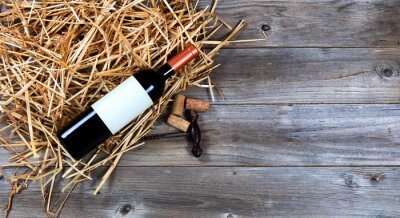Obraz Butelkę czerwonego wina z rocznika korkociąg do wina na słomie