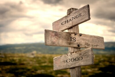 Obraz Change is good quote on wooden signpost in nature with moody background. Motivational, move on, changes, choice, choices concept.