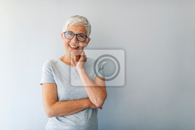 Obraz Close up portrait of a professional business woman smiling. Portrait of cheerful mature woman standing against grey wall. Close up portrait of beautiful older woman smiling and standing by wall