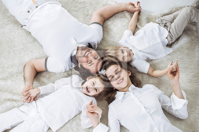 Obraz concept of family happiness: happy family relaxing on the carpet on Sunday