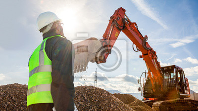 Obraz construction worker or engineer on construction site with excavator
