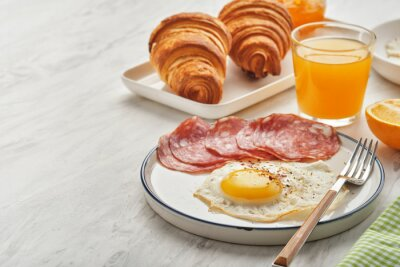 Obraz Continental breakfast. Fried eggs and sausage with croissants and orange juice.