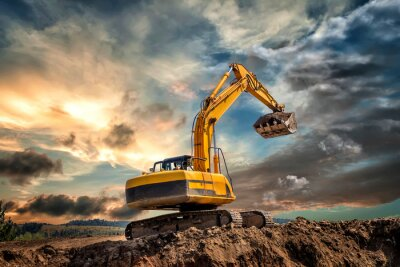 Obraz Crawler excavator during earthmoving works on construction site at sunset