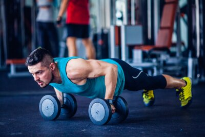 Obraz Crossfit instruktor na siłowni robi pompki