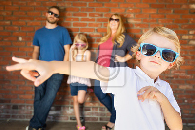 Obraz Cute Young Caucasian Boy Wearing Sunglasses with Family Behind
