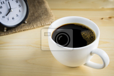 Czarna kawa w filiżance kawy na drewnianym tle