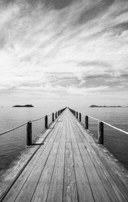 Obraz Czarny i biały krajobraz drewniany most w błękitnym morzu na tropikalnej plaży.