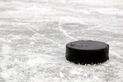 czarny krążek hokejowy na lodowisku