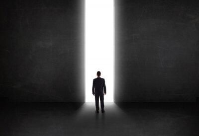 Obraz człowiek biznesu patrząc na ścianę światłem otwarcia tunelu