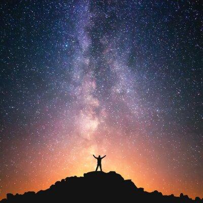 Obraz Człowiek i Wszechświat. Człowiek stoi na szczycie wzgórza obok Drogi Mlecznej z rękami podniesione do powietrza.