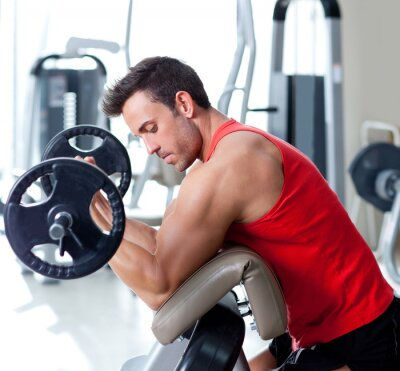 Obraz Człowiek ze sprzętem treningu siłowego na siłowni sportu