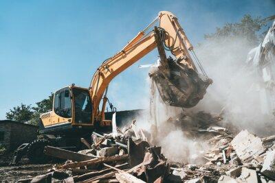 Obraz Destruction of old house by excavator. Bucket of excavator breaks concrete structure.