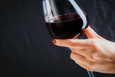 Obraz Dłoń trzymająca kieliszek czerwonego wina na ciemnym szarym tle