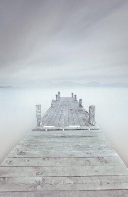 Obraz Drewniane molo na jeziorze w nastroju pochmurny i mglisty.