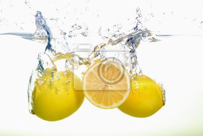 Obraz Dwa cytryny i cytryna plasterek bryzgają w wodzie na białym tle