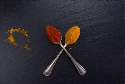 Obraz Dwa zabytkowe łyżki z przyprawami curry i papryki na czarnym tle.