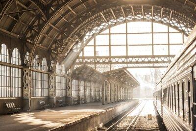 Obraz Dworzec kolejowy kryty wschód słońca słońce w sepii. Przewóz i platforma z dachem konstrukcyjnym. Podróżować pociągiem kolejowym