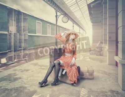 Obraz Dziewczynka siedzi na walizce czeka na retro stacji kolejowej. Styl zabytkowe karty kolorów