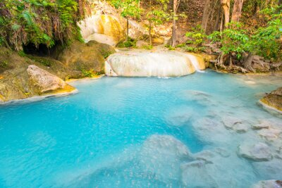 Emerald blue lake with rock cascades of stream waterfall in tropical jungle forest. Landscape of Erawan National park, Kanchanaburi, Thailand