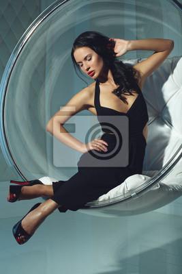 Obraz Erotyczna dziewczyna z ciemnymi włosami, siedzi na krześle rundzie
