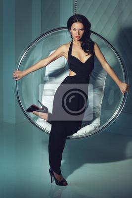 Erotyczna dziewczyna z ciemnymi włosami, stoi w pobliżu okrągłego krzesła
