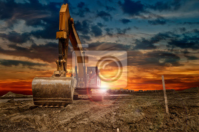 Obraz Excavating machinery at the construction site, sunset in background.