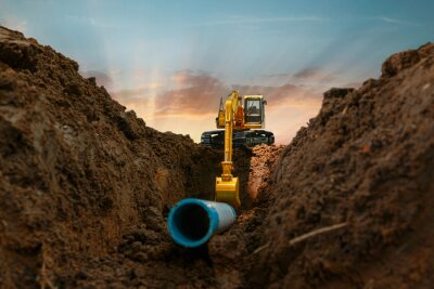 Obraz Excavator is digging in the construction site pipeline work on sunset sky background