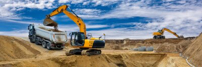 Obraz excavator working on construction site with dramatic sky