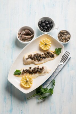 Obraz filet z ryby z czarnymi oliwkami kaparami i anchois