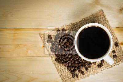 Filiżanka kawy i palonych ziaren kawy na drewnianym stole.