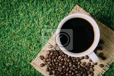 Filiżanka kawy i palonych ziaren kawy na trawie.